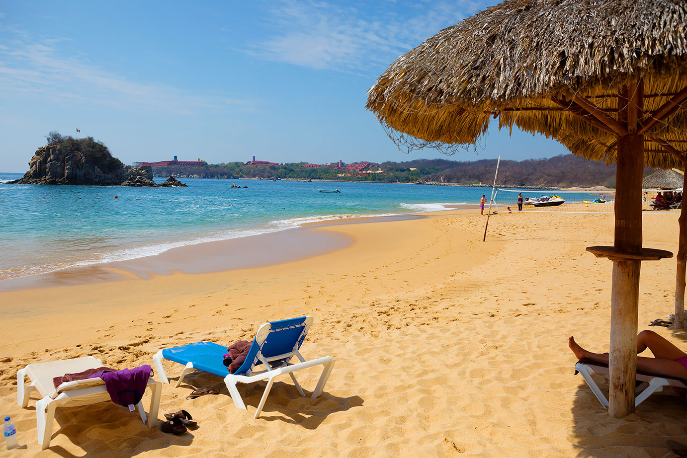 Two lounge chairs and a thatched umbrella on a sandy beach on the Huatulco coast