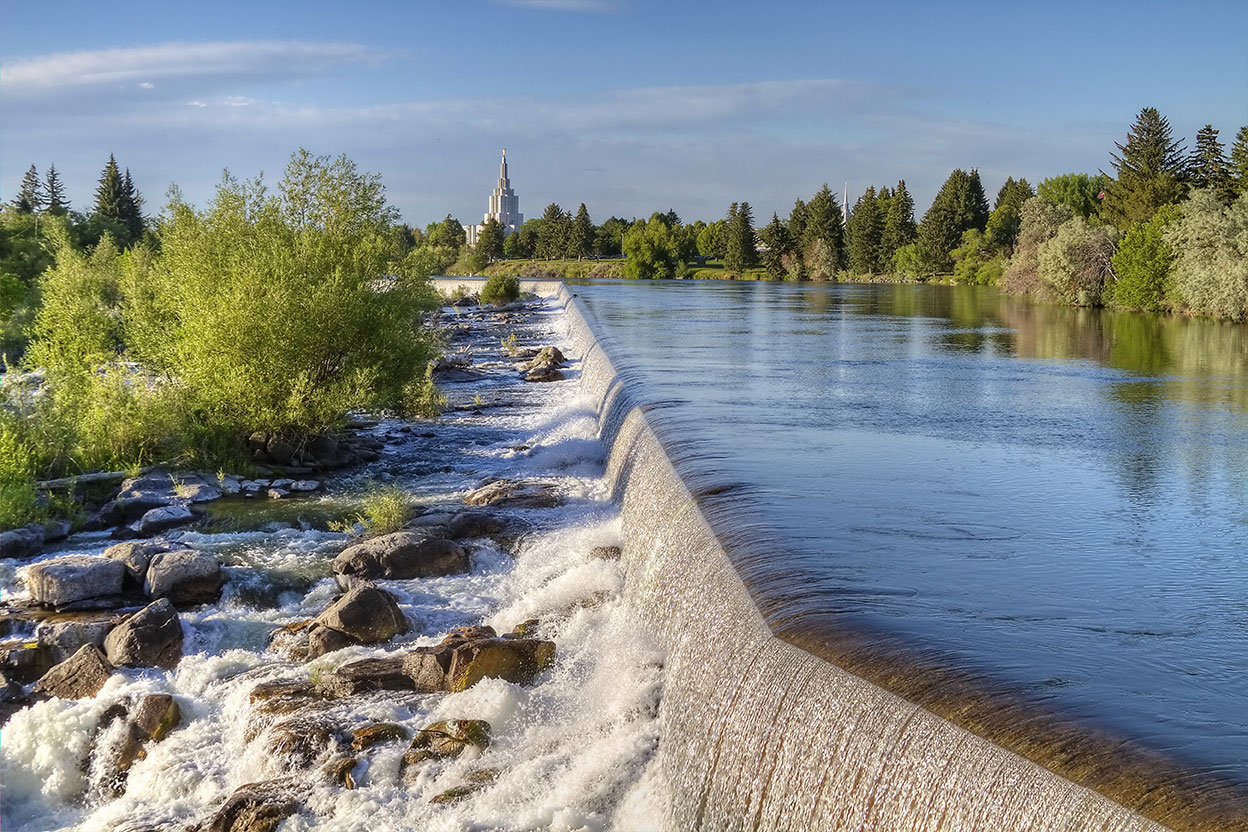 Water rushes over a dam onto rocks in Idaho Falls