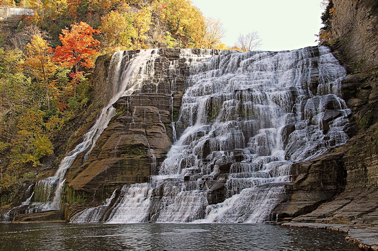 A wide waterfall amongst autumn trees in Ithaca