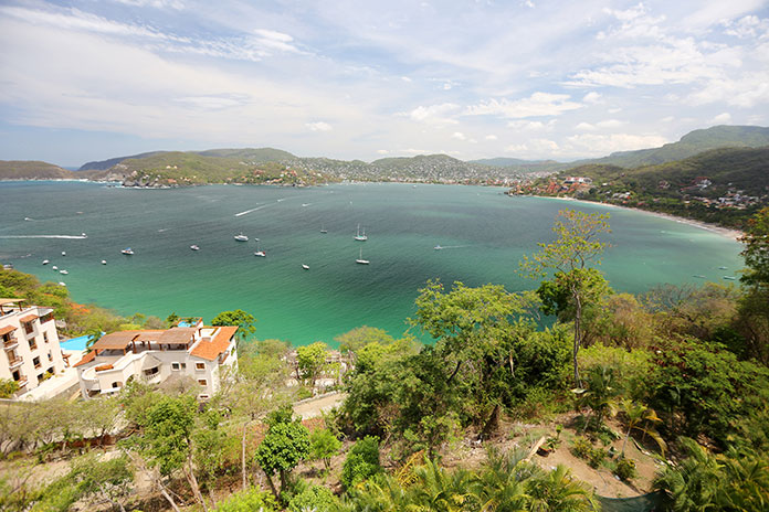 Blue-green water next to tropical foliage in Ixtapa-Zihuatanejo
