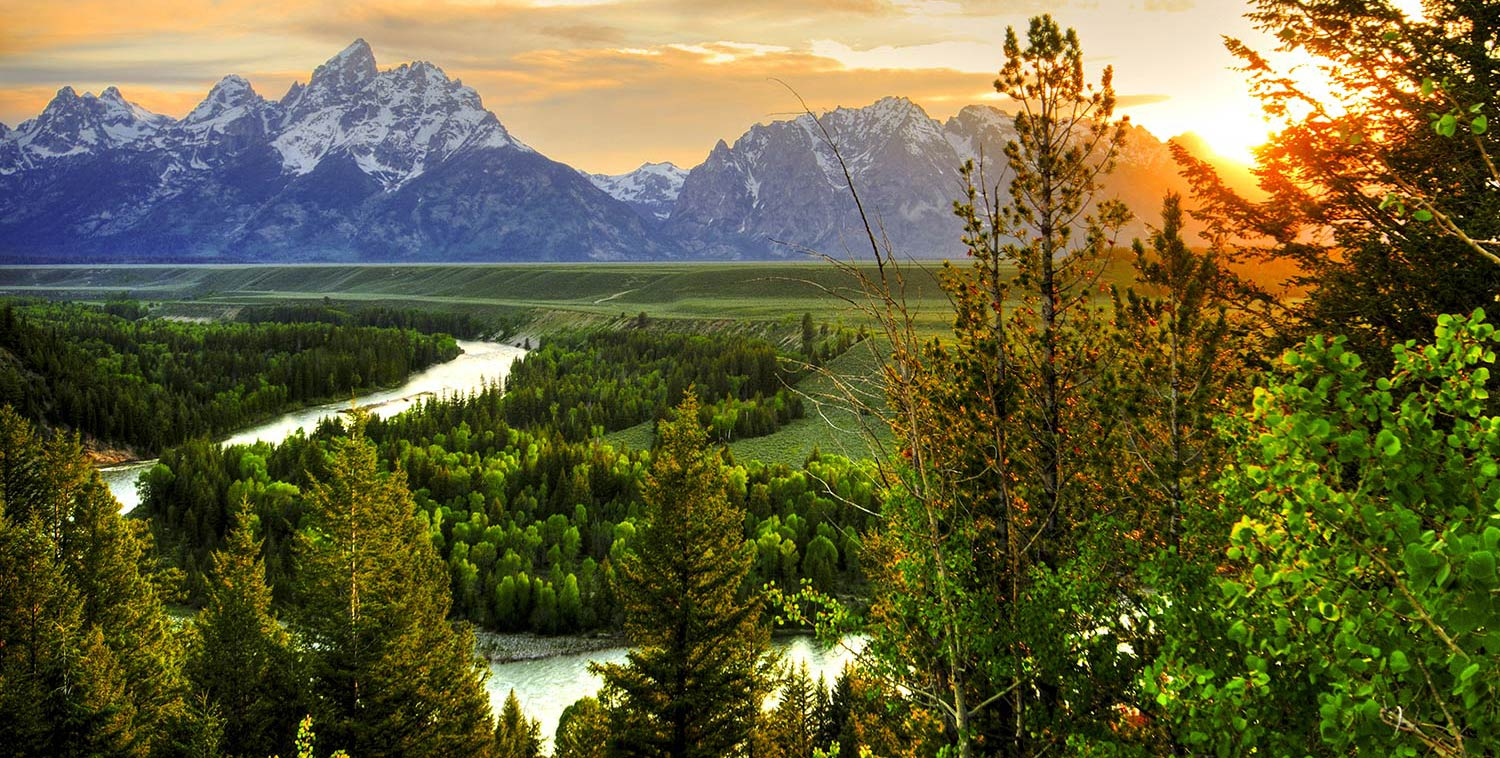 A winding river cuts through deep green forest at sunset with a view of snowcapped mountains in the background of Jackson Hole