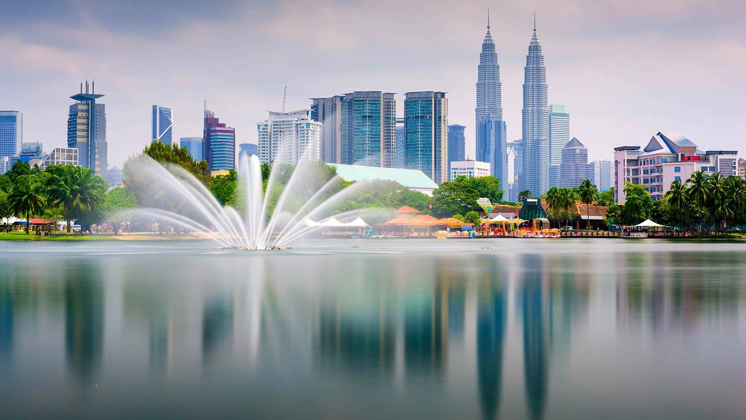 A fountain sprays in multiple directions in front of downtown Kuala Lumpur