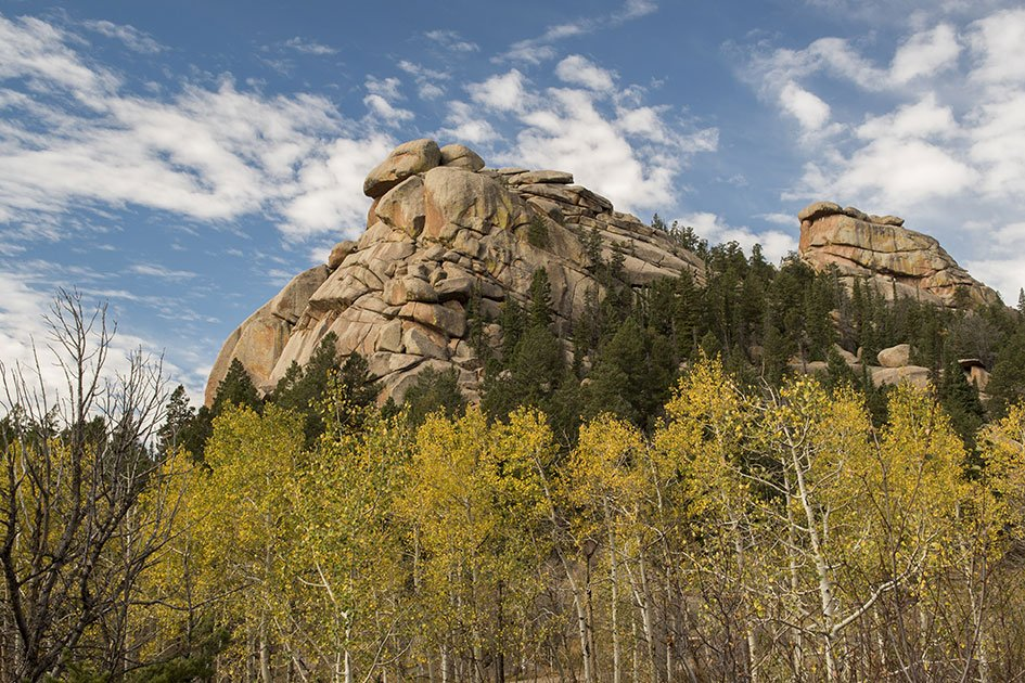 Large rock formation towers over thin yellow-green trees in Laramie
