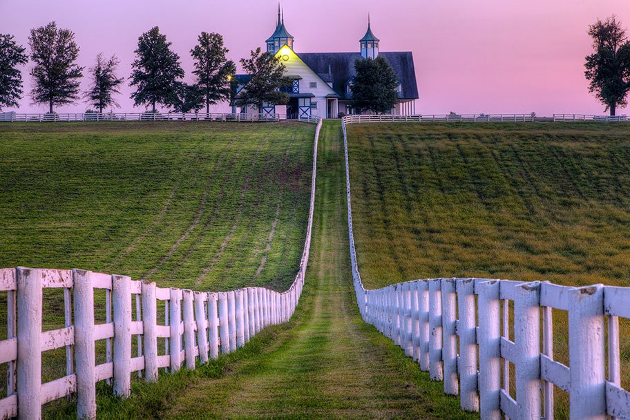 Two white wooden fences lead the way to a white building in Lexington at dusk
