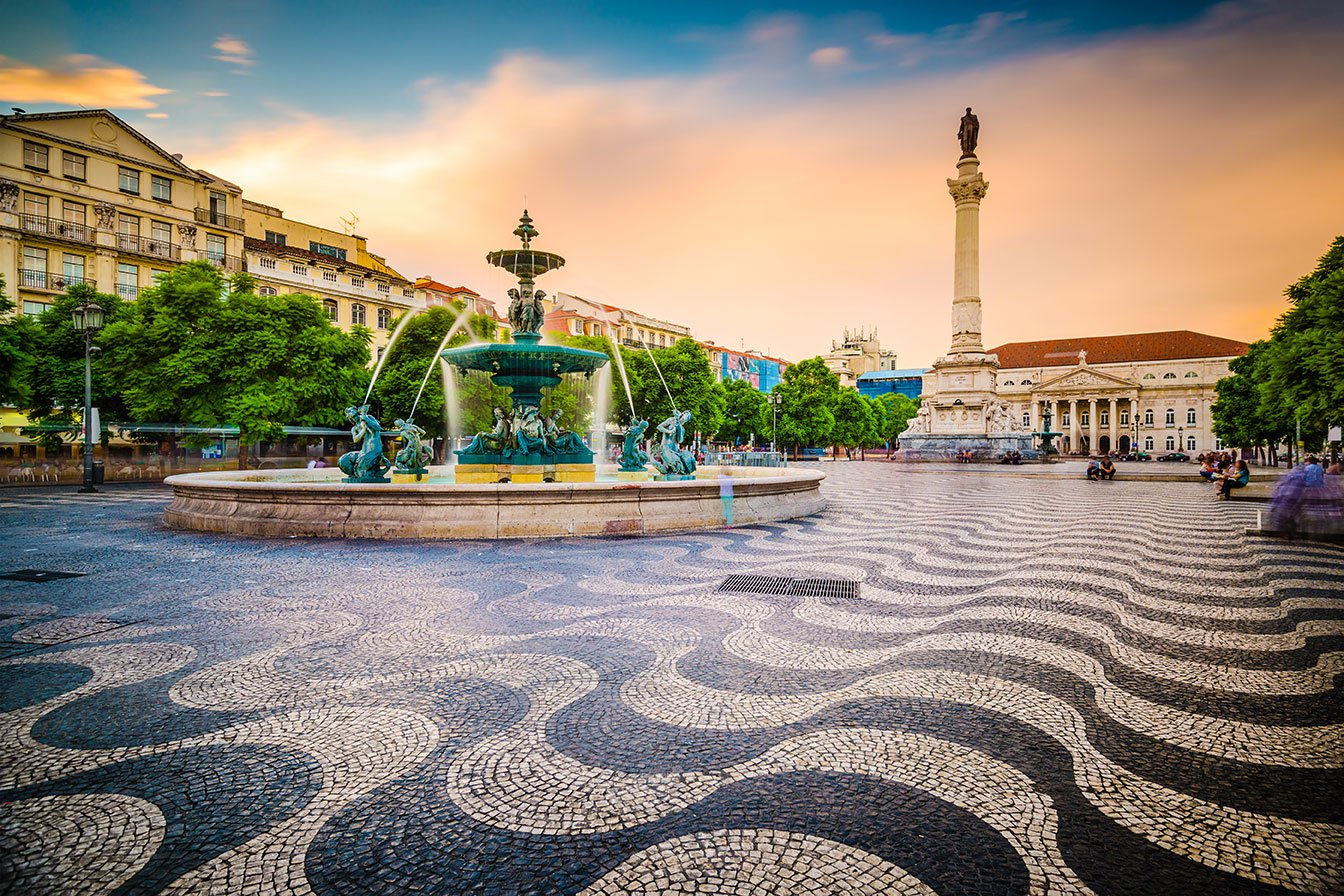 A fountain flows above the black and white wavy patterned ground in Lisbon