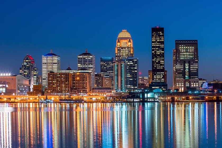 Illuminated buildings reflect off the water in Louisville