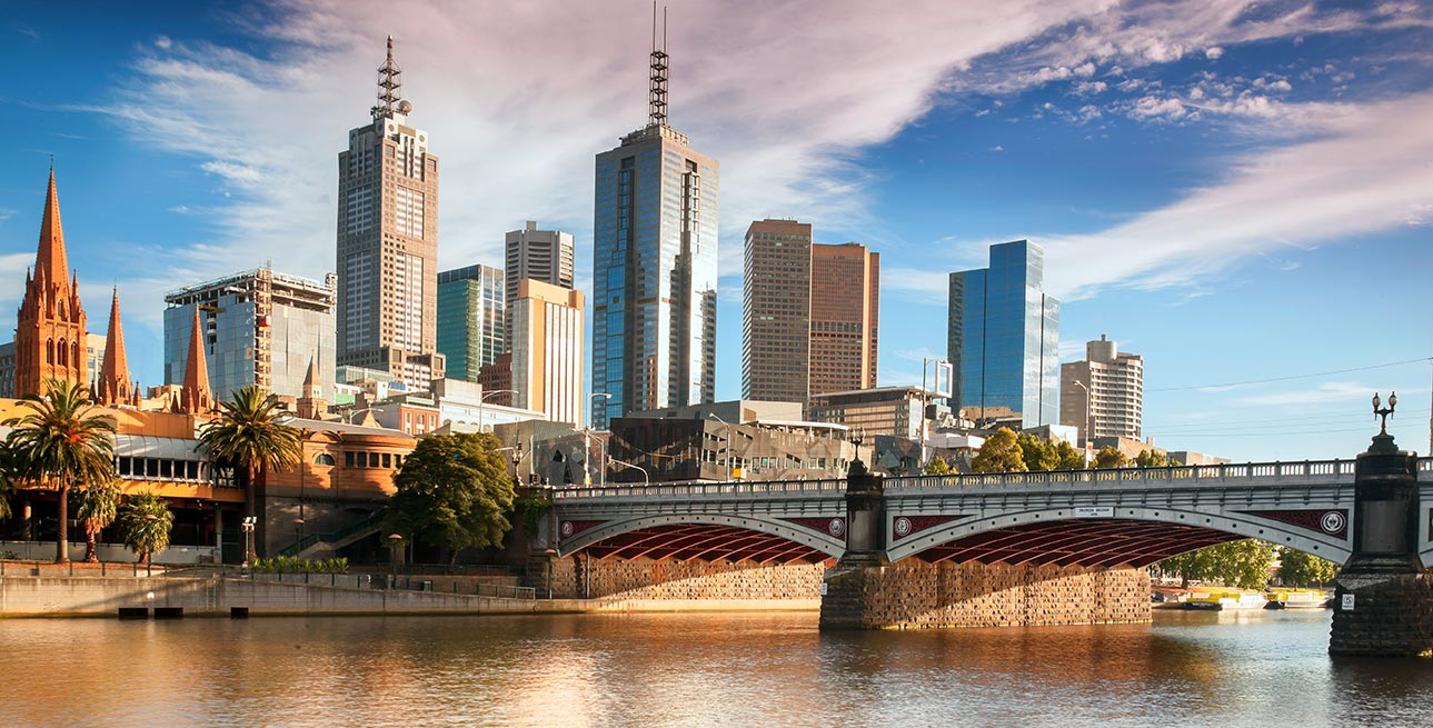 Urban skyscrapers adjacent to a bridge over water in Melbourne