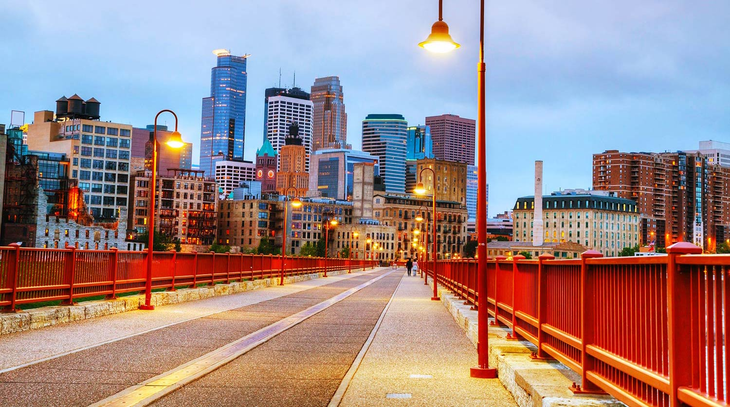 Illuminated street lined with red fences leads into downtown Minneapolis