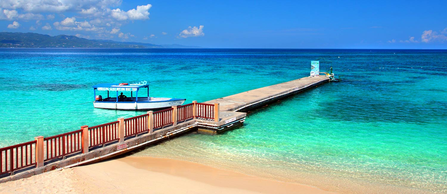 A long wooden dock extends into shades of turquoise waters in Montego Bay