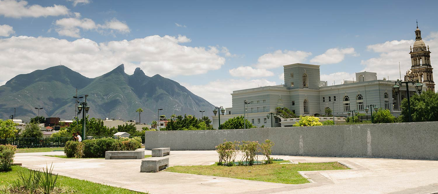 White buildings adjacent to a large mountain in Monterrey