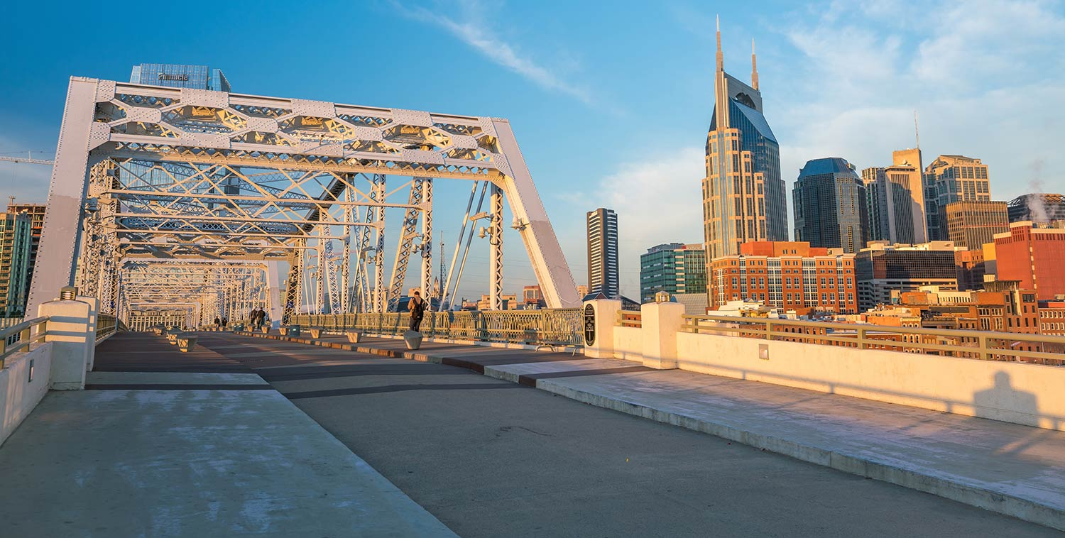 A metal bridge adjacent to downtown Nashville at sunset