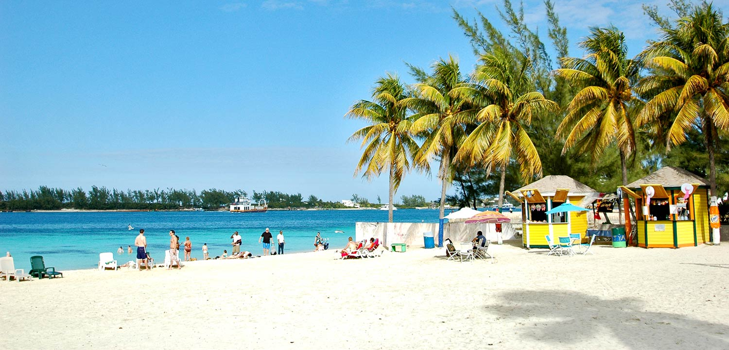 Palm trees and small wooden huts on white sand next to turquoise water in Nassau