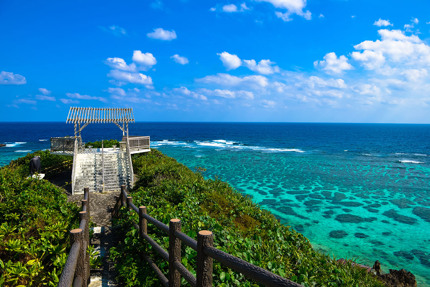 A wooden pier surrounded by foliage leads into multi-shade blue water in Okinawa