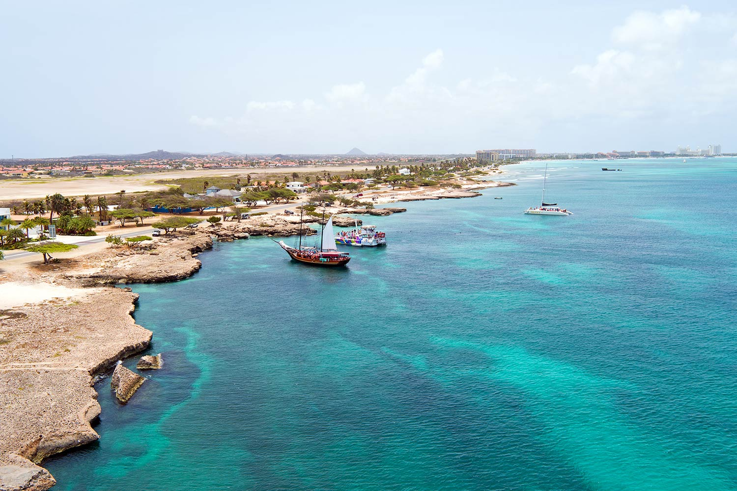 Several boats bob just off a the jagged coastline of Oranjestad