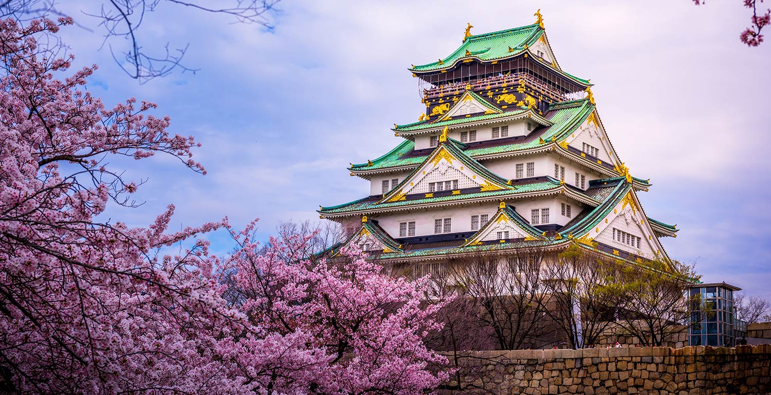 Oriental castle surrounded by cherry blossoms in Osaka