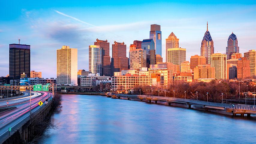 A river runs alongside skyscrapers in Philadelphia at sunset