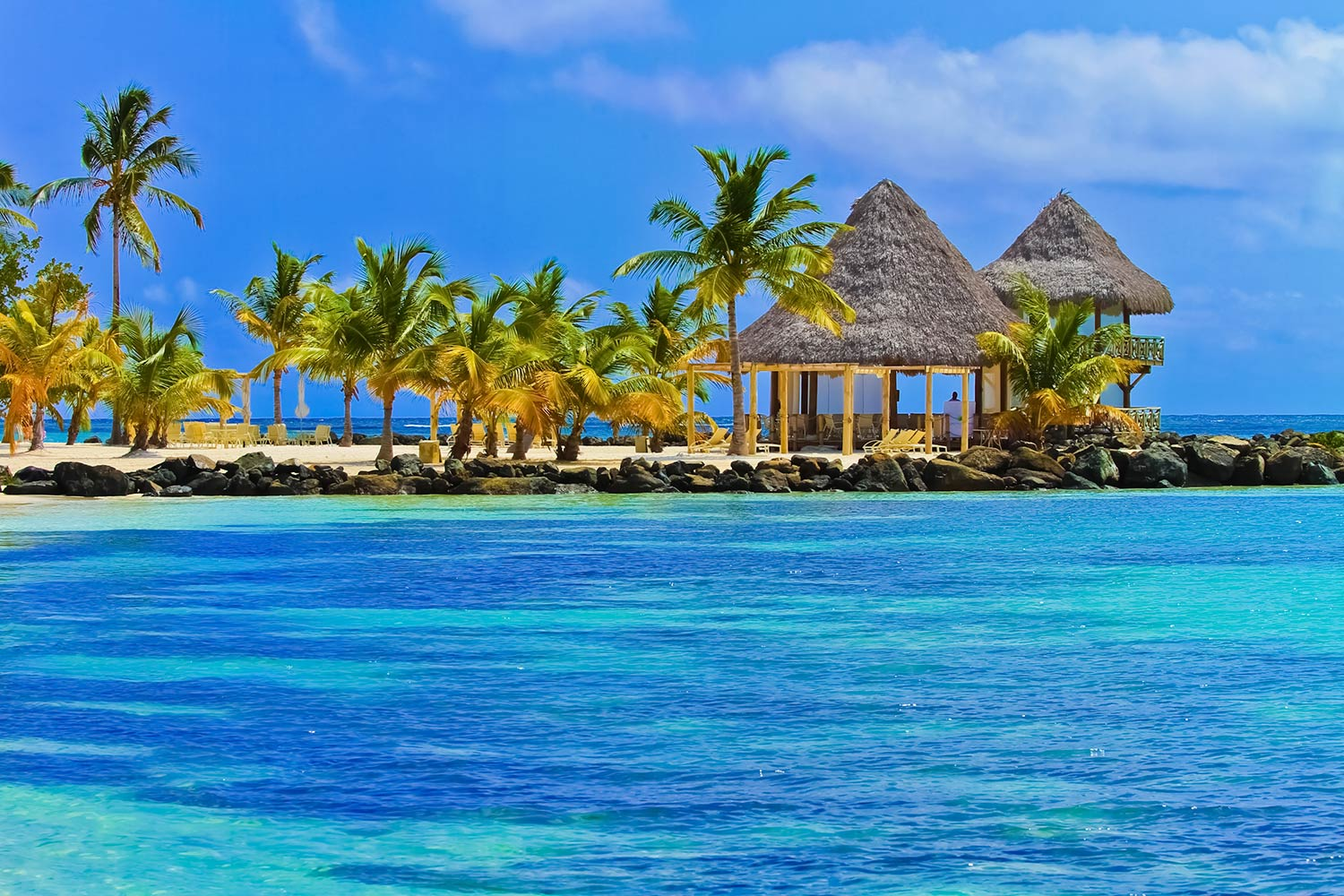Thatched hut surrounded by palm trees next to bright blue water in Punta Cana